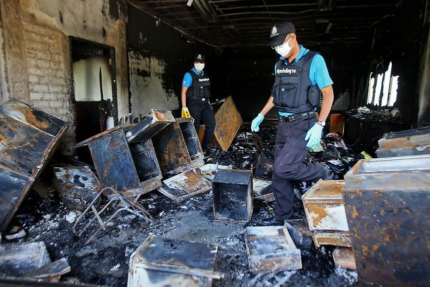 Thai forensic police inspect the burnt remains of the district government bureau after it was allegedly set alight by Muslim militants in Pattani province on Oct 28, 2014.-- PHOTO: AFP