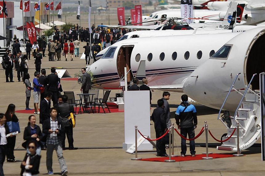 Guests walk next to aircraft during the Asian Business Aviation Conference and Exhibition (ABACE) at Hongqiao International Airport in Shanghai in this April 15, 2014. -- PHOTO: REUTERS