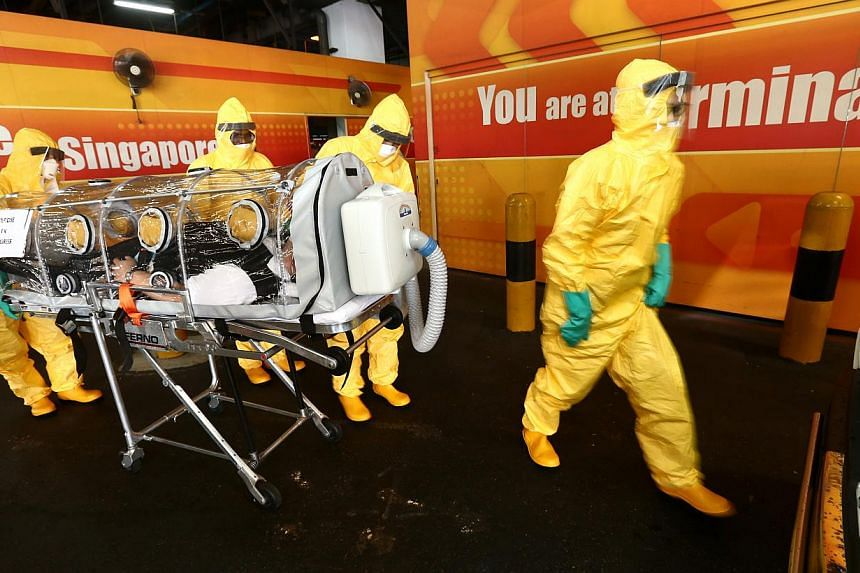 Workers in protective gear attending to a mock Ebola patient, in an exercise to demonstrate Singapore's defence against highly infectious diseases, at Changi Airport's Terminal 2 on Aug 14, 2014. -- PHOTO: ZAOBAO