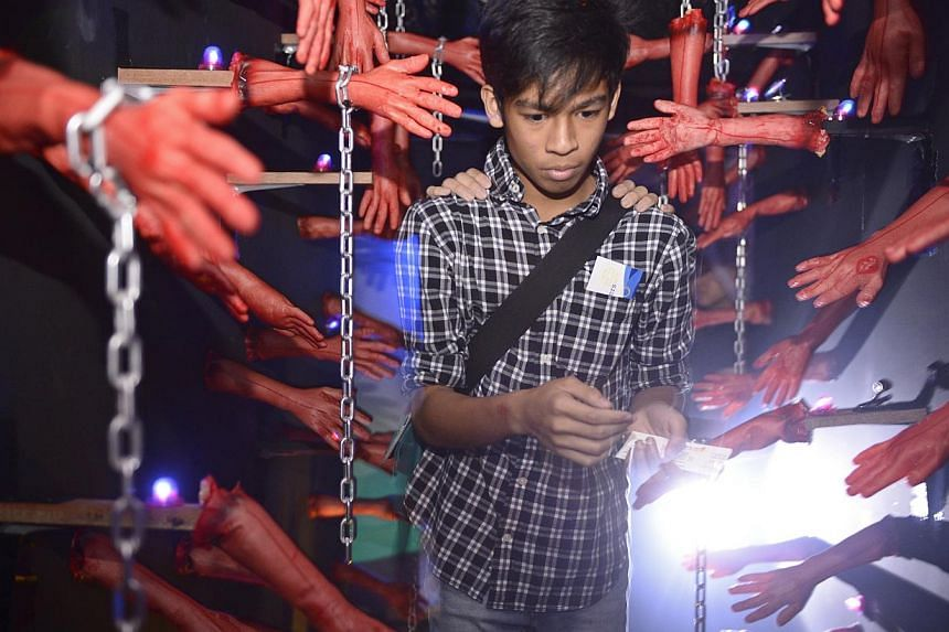 A boy walks through the Room Full of Hands at the Doors to 'Hell'oween - The terror maze at D'Marquee, at Downtown East. -- ST PHOTO: MARK CHEONG