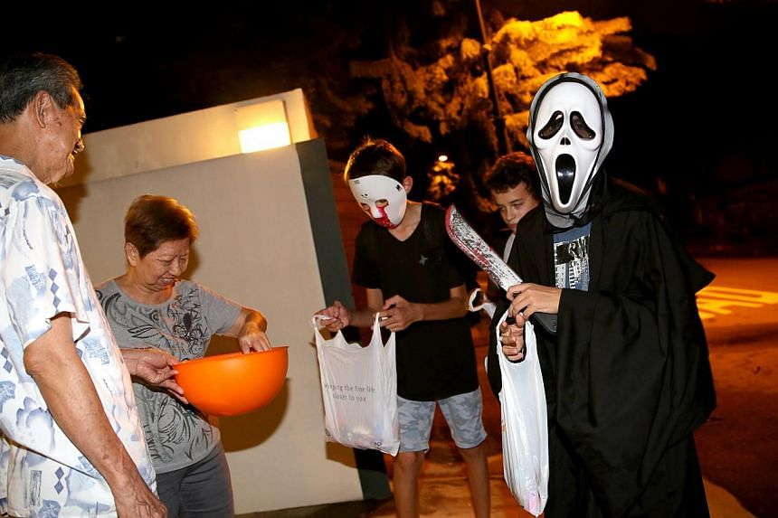 Mdm Tan Ah Moi, 77, and Mr Ho Seng Sock, 81, giving out sweets to children on Halloween night in Serangoon Gardens. -- ST PHOTO: WANG HUI FEN