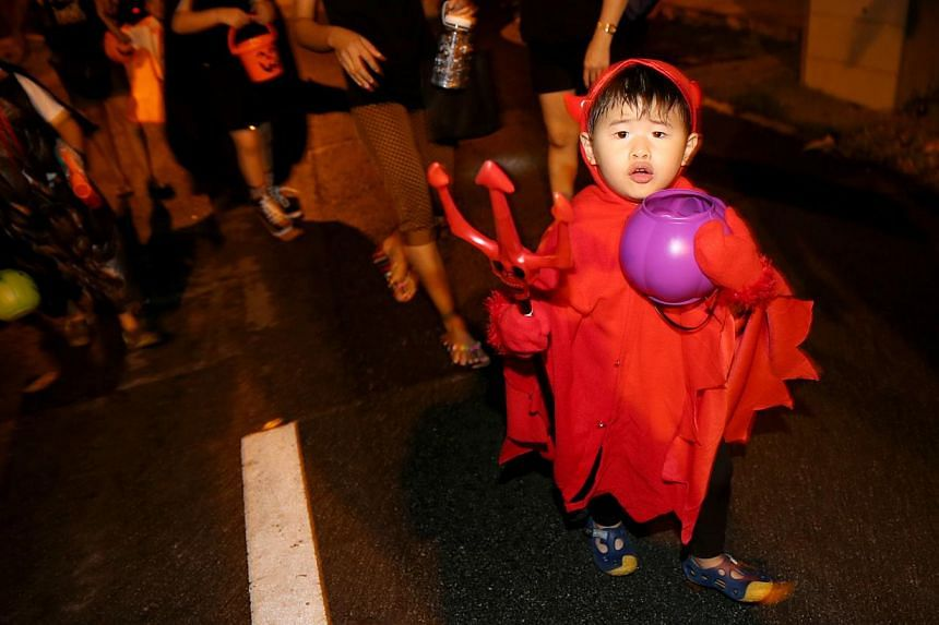 A boy dressed in Halloween costume guarding his bucket filled with candies in Serangoon Gardens. -- ST PHOTO: WANG HUI FEN