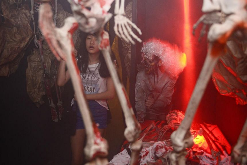 A girl walks pass a zombie in the Skeleton Alley at the Doors to 'Hell'oween - The terror maze at D'Marquee, at Downtown East. -- ST PHOTO: MARK CHEONG