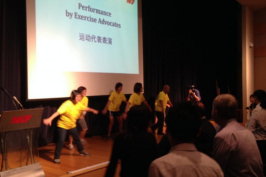 National Kidney Foundation's exercise specialist and dialysis patients leadingManpower Minister Tan Chuan-Jin, NKF chief executive Edmund Kwok and other guests in exercises at the inaugural Extraordinary Employer and Courage Awards Ceremony at