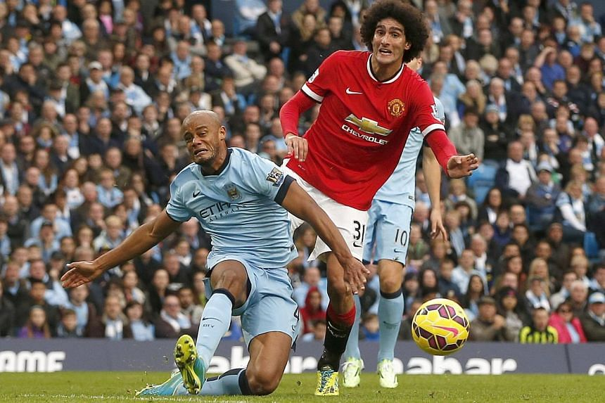 Manchester City's Vincent Kompany (left) falls in front of Manchester United's Marouane Fellaini during their English Premier League match at the Etihad Stadium in Manchester on Nov 2, 2014. -- PHOTO: REUTERS