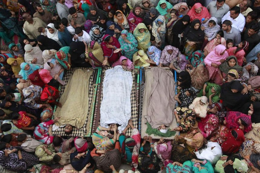 Relatives gathering on Monday beside the bodies of victims who were killed on Sunday's suicide bomb attack on the Wagah border, before funeral prayers in Lahore. At least 45 people were killed on Sunday when a suicide bomber blew himself up on the Pa