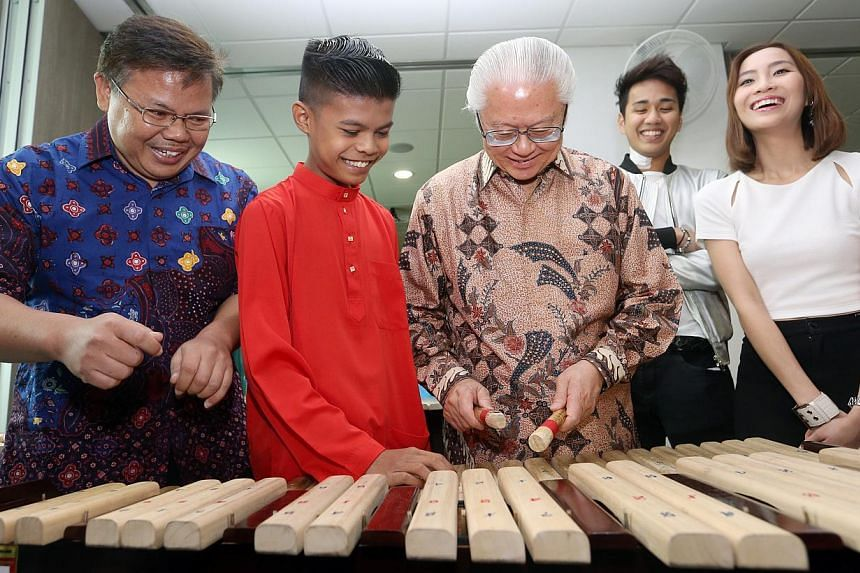 (From left) Music instructor Budi Hartiana, and Ain beneficiary Zainul Aladdin Azfar giving President Tony Tan Keng Yam a quick lesson on the musical instrument kolintang. With them are 98.7FM DJs Joachim Gomez and Sonia Chew. -- ST PHOTO: SEAH KWANG