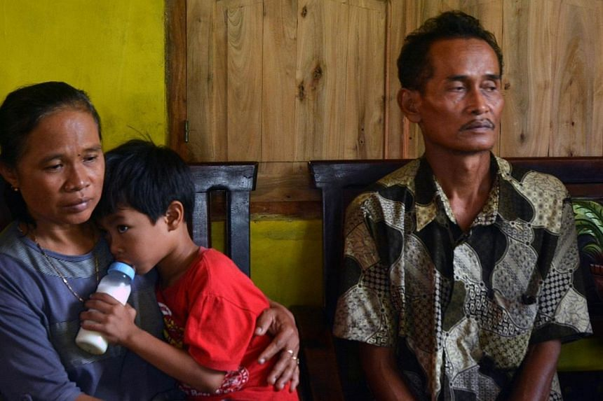 The Indonesian parents of Miss Sumarti Ningshi, the Indonesian woman was murdered in Hong Kong - mother Suratmi, (left) carrying Muhammad Hafidz Arnovan, the five-year-old son of Miss Sumarti, and father Ahmad Kaliman (right) - in their family reside