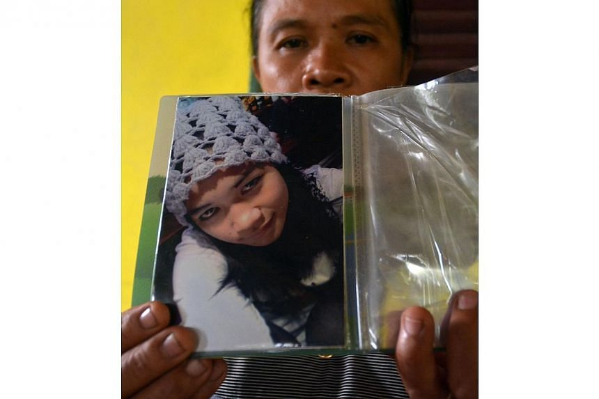 Madam Suratmi, the mother of Miss Sumarti Ningshi, an Indonesian woman who was murdered in Hong Kong, displaying a portrait of her daughter at their family residence in Cilacap, a port town on the south coast of Java island, on Nov 4, 2014. -- PHOTO: