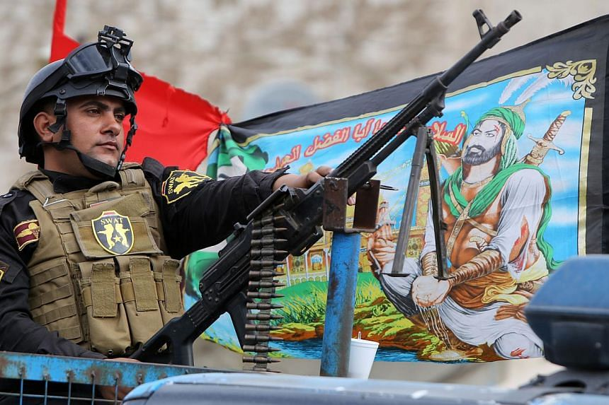 A member of Iraq's special forces keeps watch during a parade ahead of the Shiite holiday of Ashura in Baghdad's northern district of Kadhimiya on November 3, 2014. -- PHOTO: AFP