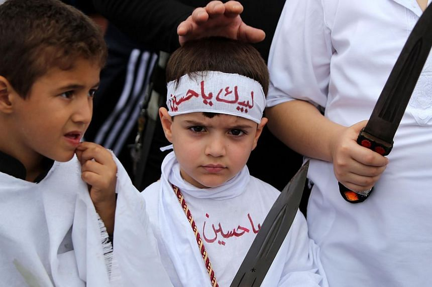 Iraqi Shiite boys take part in a self-flagellation ceremony during a parade ahead of Ashura. -- PHOTO: AFP