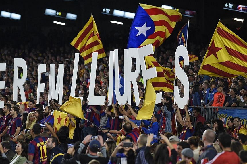"""Chong Zi Liang/SPH: Barcelona Football Club supporters holding up placards that say """"we are free"""" and waving Catalan flags during Barcelona's clash with Celta Vigo at the Camp Nou on Nov 1, 2014. -- PHOTO: AFP"""