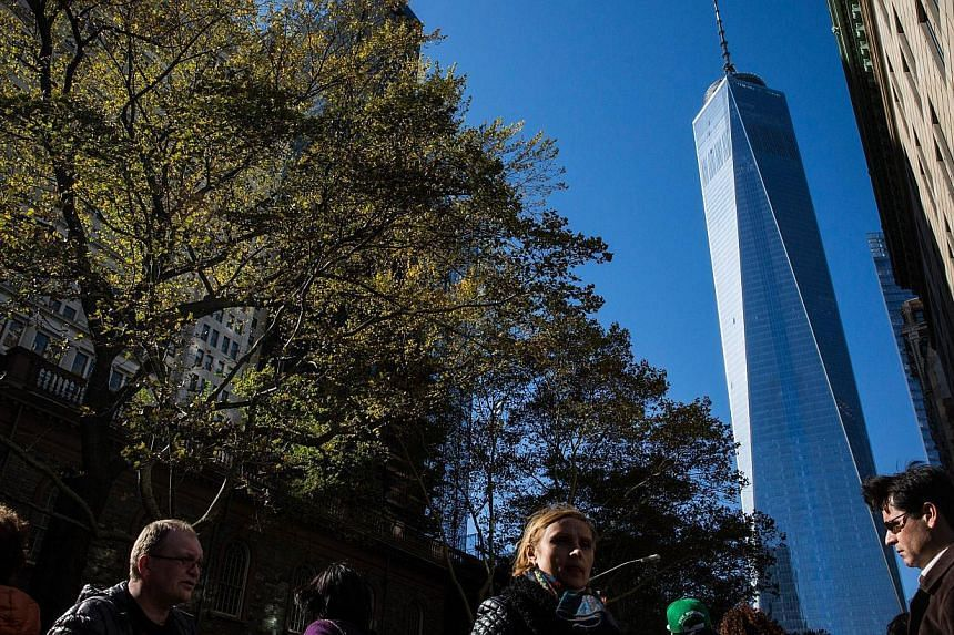 People walk past One World Trade Center, which opened in New York City on Nov 3, 2014. -- PHOTO: AFP