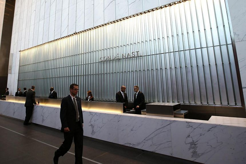 Conde Nast employees work in the lobby of the One World Trade Center tower in New York, on Nov 3, 2014. -- PHOTO: REUTERS