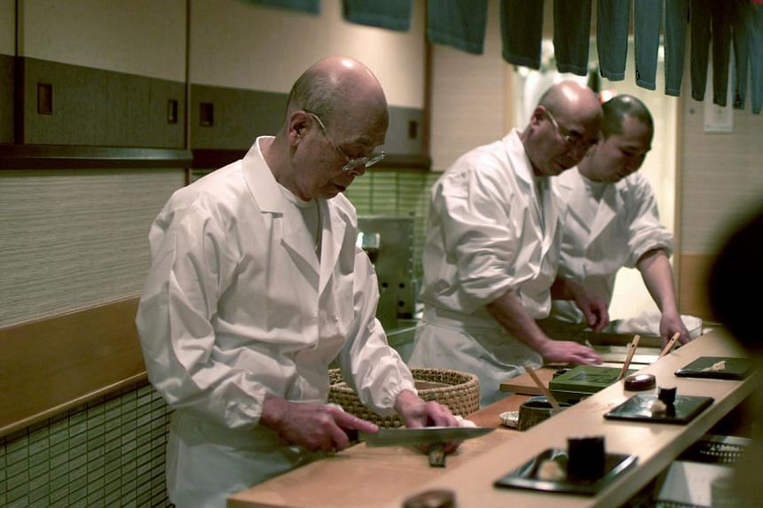 Master sushi chef Jiro Ono and his team creating sushi. He shot to international fame when the Michelin guide gave his modest sushi bar the highest accolade of three stars. -- PHOTO: PREFERRED CONTENT