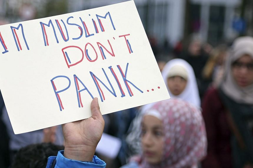 "A demonstrator holds up a sign reading ""I'm Muslim don't panic"" during a protest against Islamophobia in front of the Brussels' Justice Palace on Oct 26, 2014. -- PHOTO: REUTERS"