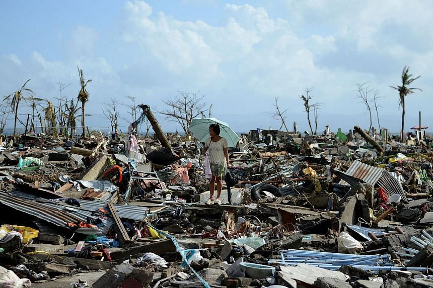 A person walks among the debris of houses destroyed by Super Typhoon Haiyan in Tacloban in the eastern Philippine island of Leyte. -- PHOTO: AFP