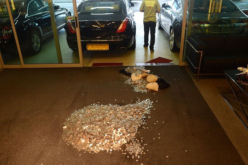 The $19,000 of coins that were left at car dealer Exotic Motors' showroom on Tuesday. -- PHOTO: LIANHE WANBAO
