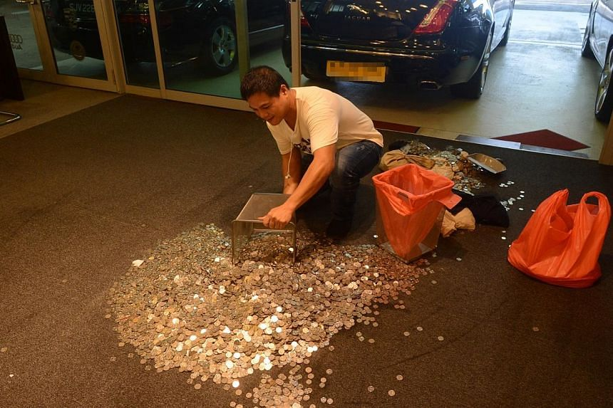 Exotic Motors employee with the $19,000 in coins, which were left at the car dealer's showroom on Tuesday. -- PHOTO: LIANHE WANBAO