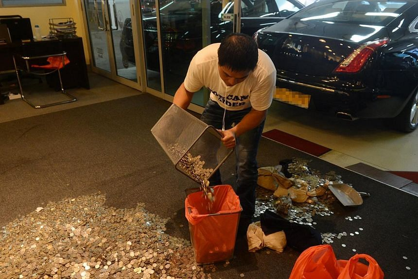 An employee of Exotic Motors putting the coins in a plastic bag. Mr Lester Ong Boon Lin, who was ordered by the court to pay Exotic Motors $19,000, paid the amount in coins on Tuesday. -- PHOTO: LIANHE WANBAO