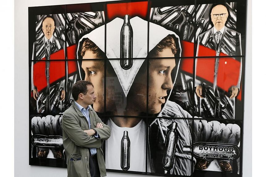 """A man watches """"Boyhood"""", a 2013 mixed media piece by artists Gilbert and George during the press opening of the Foire Internationale d'Art Contemporain (FIAC, International Contemporary Art Fair) at the Grand Palais on Oct 22, 2014 in Paris. -- PHOTO"""
