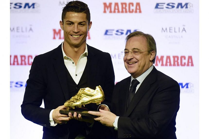 Real Madrid's Portuguese forward Cristiano Ronaldo (left) receives from Real Madrid's president Florentini Perez the 2014 Golden Boot, awarded to the European football competition's best goal scorer over the 2013-2014 season, in Madrid on Nov 5, 2014