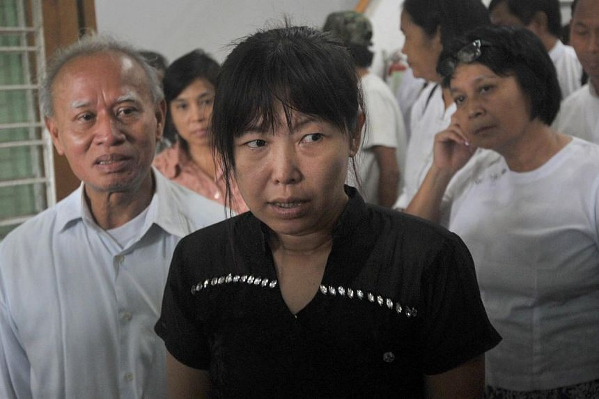 Thandar (centre) arrives at 88 Generation students office prior to a press conference about her late husband Aung Naing, in Yangon on Oct 29, 2014. The body of Aung Naing, a journalist shot dead while in the Myanmar army's custody, has been exhu