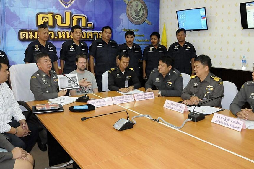 Hans Fredrik Lennart Neij (centre), a co-founder of the Swedish file-sharing website, The Pirate Bay, is surrounded by police officers at the immigration office in Nong Khai province on Nov 4, 2014.The Swedish co-founder of the Pirate Bay websi