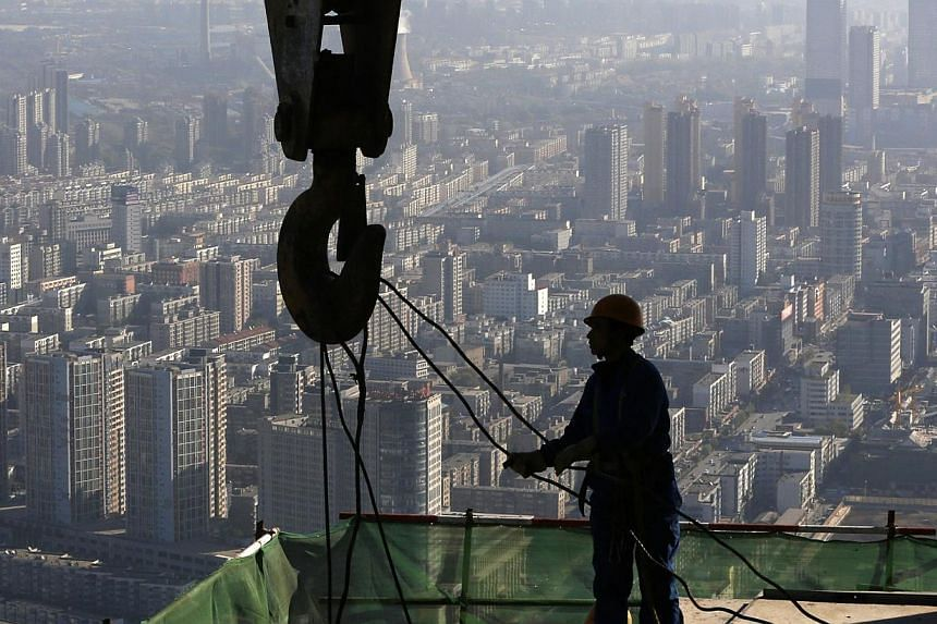 A worker operates at a construction site on the 68th storey of a building in Shenyang, Liaoning province on October 16, 2014. -- PHOTO: REUTERS