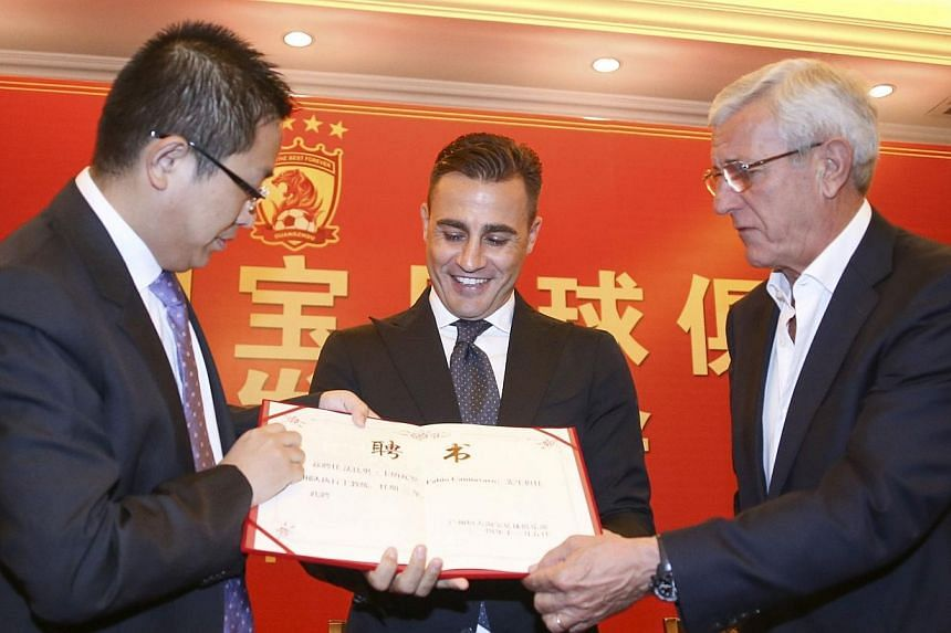 Former Italian soccer player Fabio Cannavaro (centre) receives the letter of appointment from Vice President of Evergrande Liu Yongzhuo (left) and his predecessor Marcello Lippi, during a news conference announcing him as the new coach of Chinese Sup