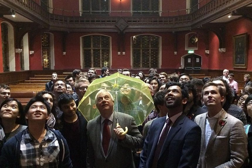Hong Kong's last British governor Chris Patten, holds a yellow umbrella -- a symbol of the Occupy movement in Hong Kong -- after it was given to him by a University of Oxford student in the audience during an event at the Oxford Union in Oxford on Oc