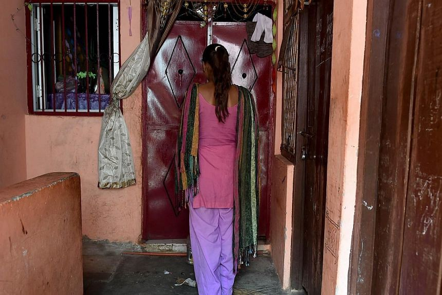 A teenage school student rape victim stands in front of the entrance to the room that she and her parents rent in a slum neighborhood in northeast New Delhi on Nov 5, 2014. An Indian man who tortured and killed his daughter's alleged rapist befo