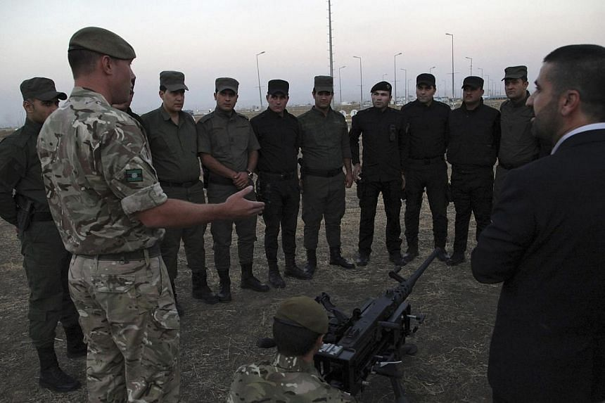 British soldiers train Kurdish Peshmerga fighters on how to use a heavy machine gun in Arbil, the capital of the autonomous Kurdish region of northern Iraq on Oct 13, 2014.Britain will boost the number of its army trainers in Iraq in the coming