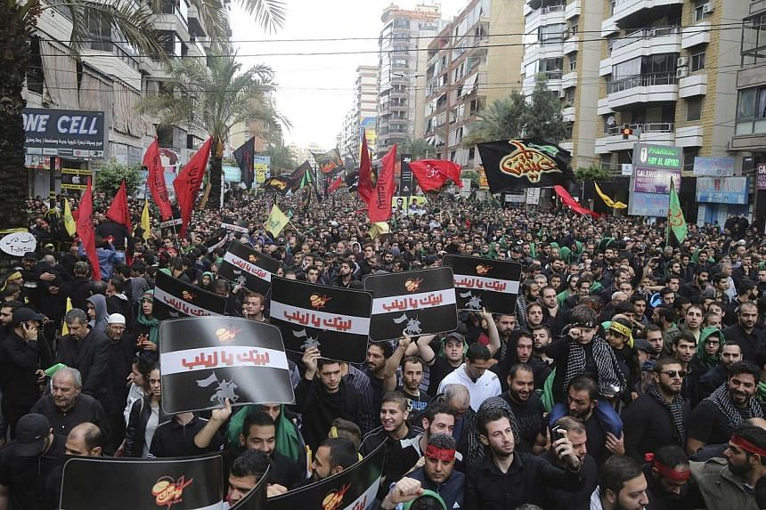 Lebanese Hezbollah supporters march during a religious procession to mark Ashoura in Beirut's suburbs on Nov 4, 2014.The head of Al-Qaeda's Syrian affiliate, Al-Nusra Front, has threatened neighbouring Lebanon in a new audio message warning tha