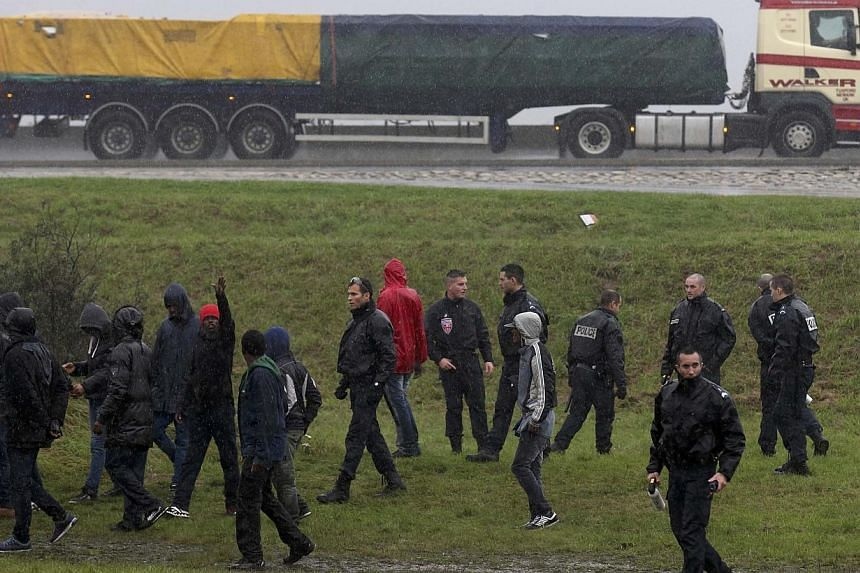 French police prevent a group of migrants from jumping onto lorries on their way to the ferry terminal in Calais on Oct 29, 2014. British officials should be sent to Calais to deter a tide of illegal migrants hoping to cross the English Channel,
