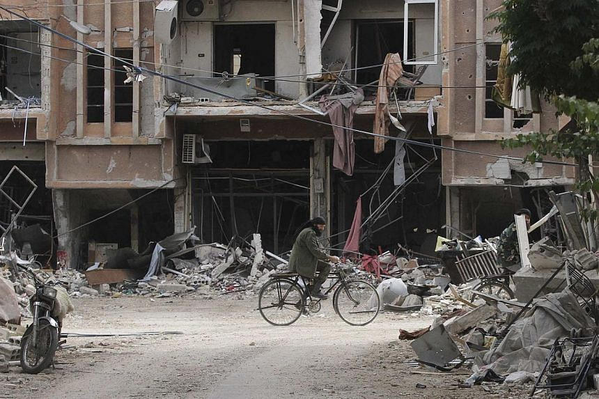 A man rides a bicycle past damaged buildings in the Damascus suburb of Jobar on Oct 28, 2014.Shelling of a rebel-held area in the north-east suburb of Qabun in the Syrian capital killed 13 children on Wednesday, a monitor said revising an earli