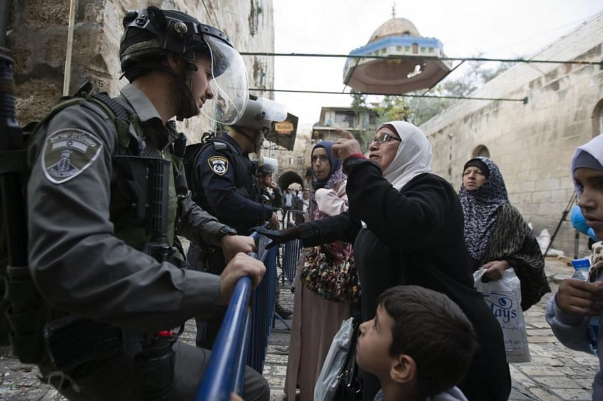 A Palestinian woman argues with an Israeli border police officer near the Lions Gate in the Old City of Jerusalem on Nov 2, 2014. Israeli police clashed with stone-throwing Palestinians inside Jerusalem's flashpoint Al-Aqsa mosque compound on We