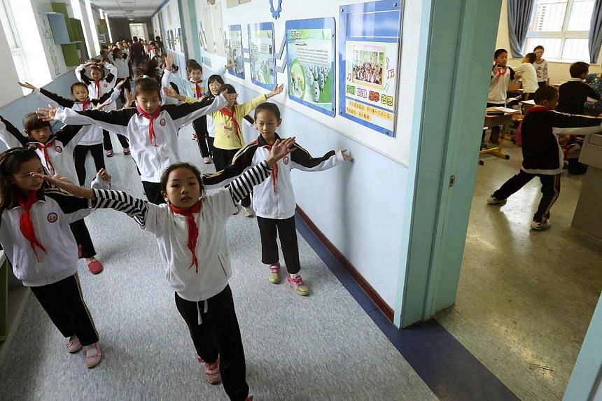 "China's Communist Party will introduce socialist values including ""freedom"" and ""democracy"" into the classroom via songs and poetry, state media said Wednesday, as the party strives to maintain its legitimacy. -- PHOTO: REUTERS"