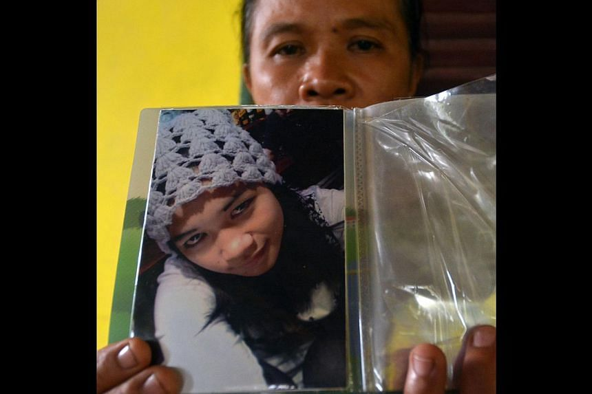 Ms Sumarti's mother Suratmi holding a picture of her daughter, whose mutilated and decomposing body was found on Saturday.