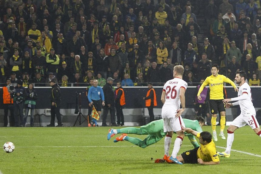 Borussia Dortmund's Sokratis Papastathopoulos (centre) scores a goal against Galatasaray's gaolkeeper Fernando Muslera during their Champions League group D soccer match in Dortmund on Nov 4, 2014. -- PHOTO: REUTERS