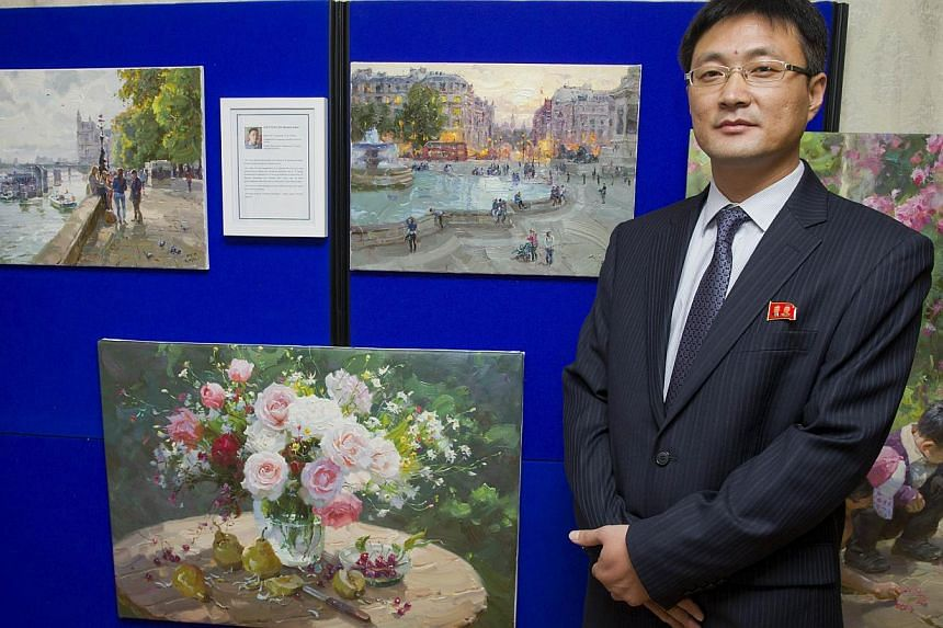 North Korean artist Jon Pyong Jin poses for a picture next to his paintings during a photocall at the North Korean embassy in west London, on Nov 3, 2014, as four artists from the Mansudae studio in North Korea exhibit their work. -- PHOTO: AFP
