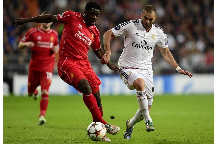 Real Madrid's French forward Karim Benzema (right) vies with Liverpool's Ivorian defender Kolo Toure during the UEFA Champions League group B football match Real Madrid CF vs Liverpool FC at the Santiago Bernabeu stadium in Madrid on Nov 4, 2014. --