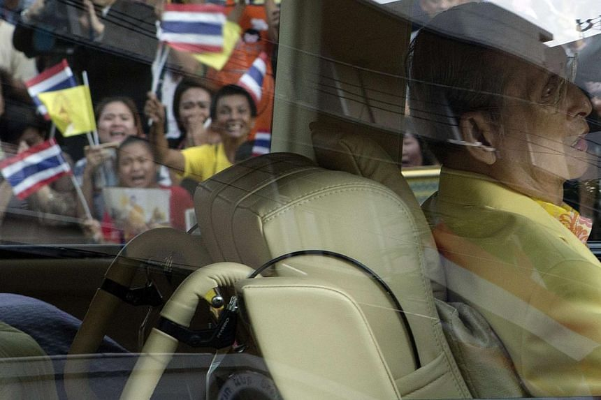 Well-wishers wave flags and pray as Thailand's King Bhumibol Adulyadej leaves Siriraj hospital in Bangkok on Sept 15. 2014.Thailand's King Bhumibol Adulyadej, the world's longest-reigning monarch, has been treated for a swollen intestine and re