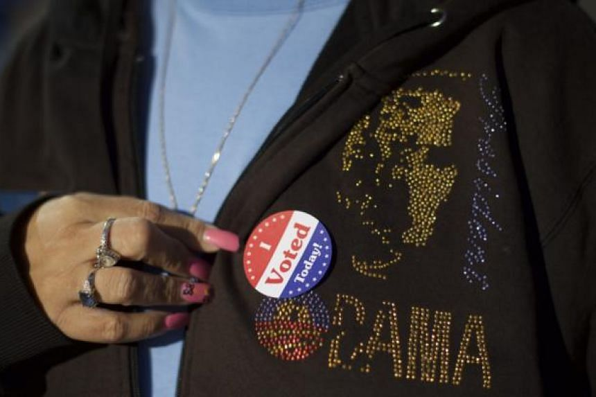 "Ms Tina Spann, 49, displaying an ""I Voted Today"" sticker on her sweatshirt with a President Barack Obama logo, after she greeted Democrat challenger for Pennsylvania Governor Tom Wolf, on election day morning in Philadelphia, Pennsylvania Nov 4, 2014"