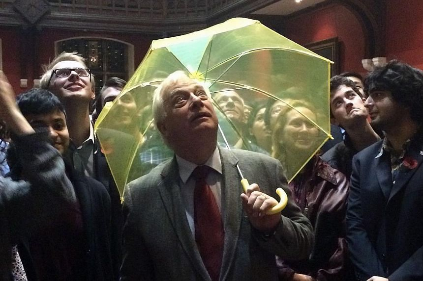 Hong Kong's last British governor Chris Patten holds a yellow umbrella - a symbol of the Occupy movement in Hong Kong - in this Oct 31 photo, after it was given to him by a University of Oxford student in the audience during an event at the Oxford Un