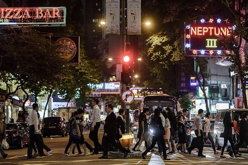Pedestrians cross a street in front of bars and restaurants in Hong Kong's Wanchai district. -- PHOTO: AFP