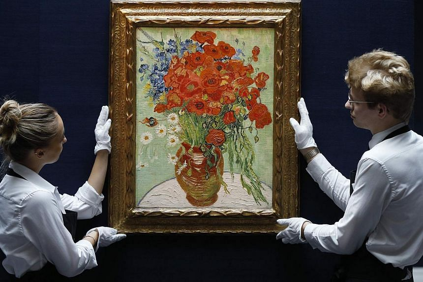 Two staff members pose in a gallery with Still Life, Vase with Daisies, and Poppies by Vincent Van Gogh from 1890 at Sotheby's auction house in London In October. -- PHOTO: REUTERS