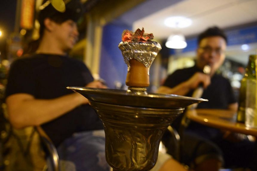 "A customer smoking a shisha or ""hookah"" pipe at a cafe on Bussorah Street on Nov 4, 2014. -- ST PHOTO: MARK CHEONG"