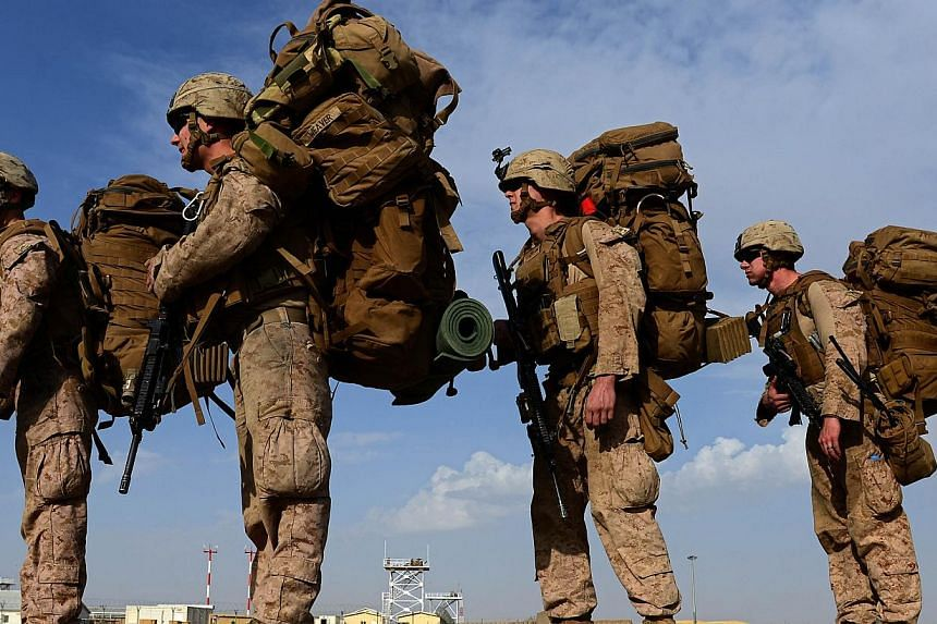 US Marines board a transport aircraft headed to Kandahar as British and US forces withdraw from the Camp Bastion-Leatherneck complex at Lashkar Gah in Helmand province, Afghanistan, on Oct 27, 2014. -- PHOTO: AFP