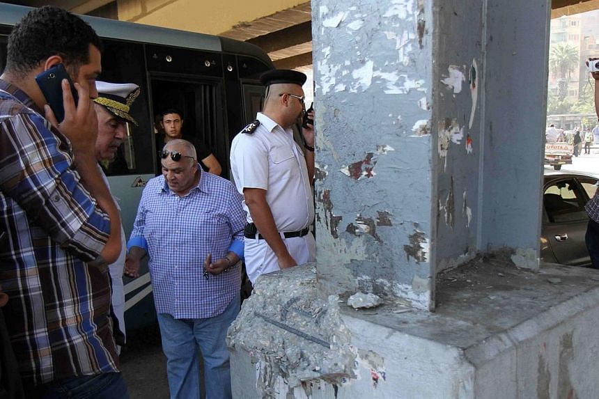 Egyptian policemen inspect the site where a small bomb which was planted under a bridge exploded near the al-Kobaa presidential palace in the northeast of Cairo on Nov 6, 2014.A bomb blast just 100 metres from a Cairo presidential palace wounde